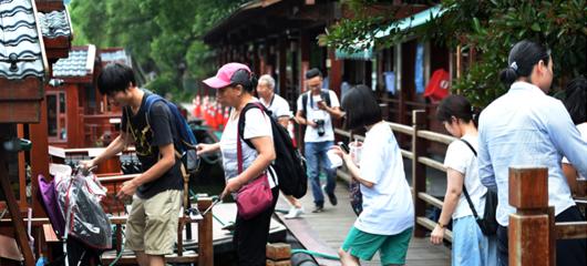 """台风""""安比""""远离杭州 西湖边游客排队乘坐游船"""