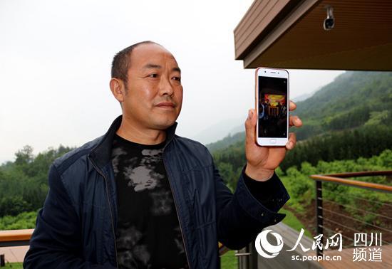 彭国华向记者展示他与恩人的照片。何孟书摄