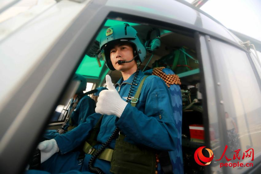 图为直升机飞行员严阵以待,准备起飞。张千摄