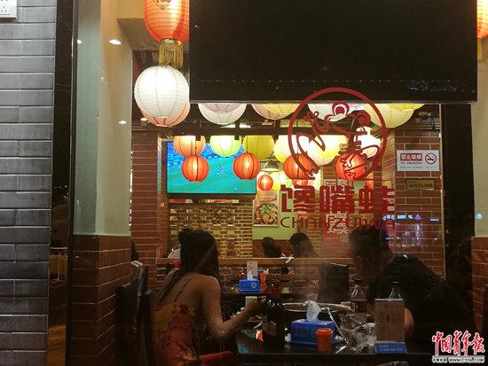 6月27日,北京簋街,吃小龙虾的人在看球赛。张渺/摄