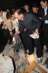 总理冒雨攀上瓦砾堆摔倒手臂出血