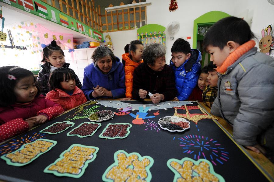 日,两名老人与幼儿园的小朋友一起用五谷杂粮贴画.-五谷 福 字送