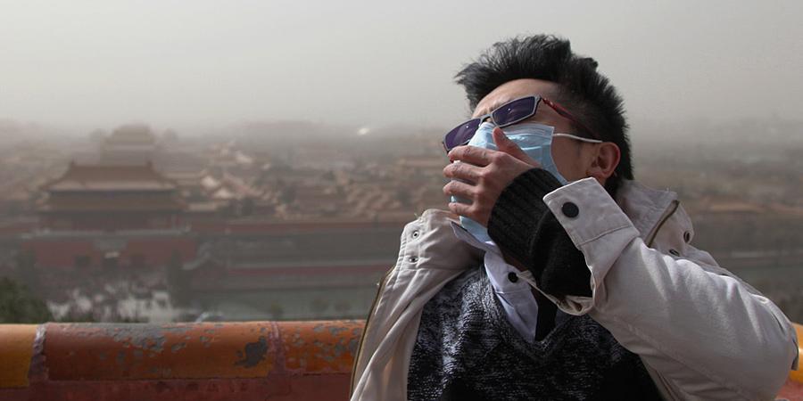 3月9日上午,漫天沙尘弥漫北京。图为一名游客冒着风沙游览景山公园