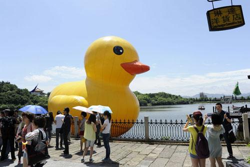 """6月3日,游客在横店影视城广州街?香港街景区内与""""大黄鸭""""合影留念。"""