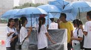 大雨突袭 大学生抱团护琴