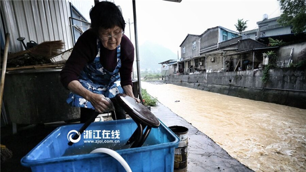 村民在清洗从洪水中捞出的桌椅家具