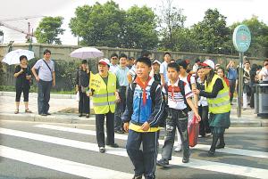 志愿者引导小学生过斑马线.-宁波市十部门联手推进 文明出行 八大活