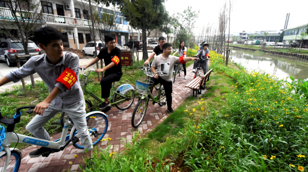 浙江台州:骑着单车巡河 倡导低碳出行